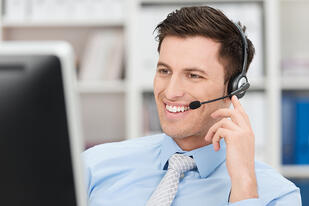 Smiling friendly handsome young male call centre operator or client services personnel beaming as he listens to a call and checks information on his computer monitor
