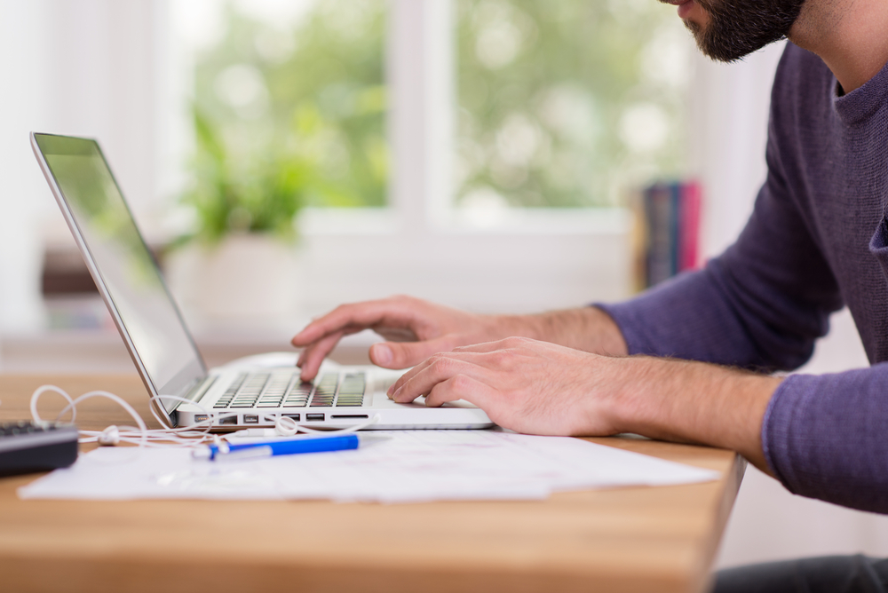 Close up low angle view of a man working from home on a laptop computer sitting at a desk surfing the internet