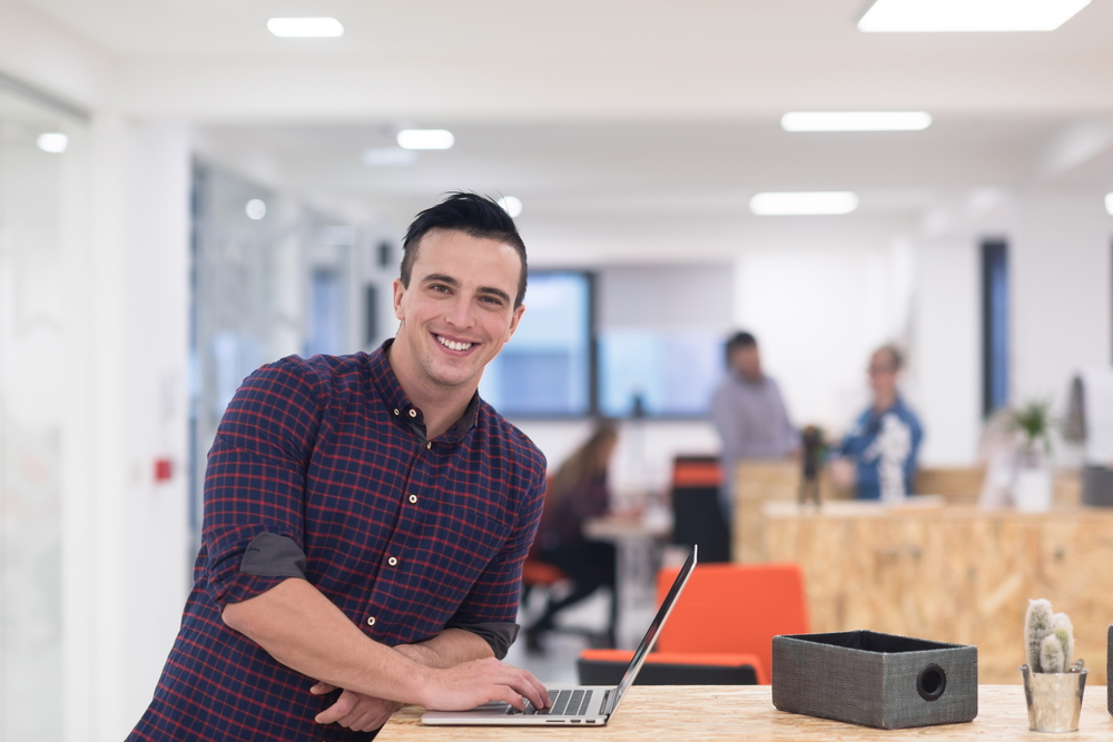 portrait of young businessman in casual clothes at modern  startup business office space,  working on laptop  computer-1